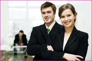 Two office workers standing smiling with confidence