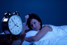 Woman in bed watching the clock at night