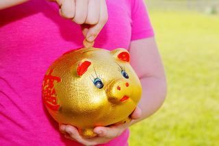 Girl Putting Money Into Piggy Bank