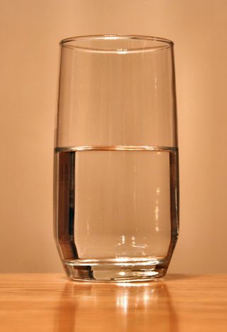 Derek Jensen/A glass of water demonstrating the eternal conundrum of whether the glass is half full or half empty, Public Domain, via Wikimedia Commons