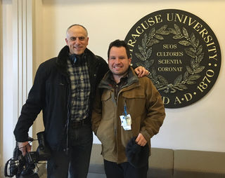 Filmmaker Dan Habib and Micah Fialka-Feldman, one of the subjects of the upcoming film Intelligent Lives (working title, due Fall 2017) stand together inside a building at Syracuse University, where Micah has attended college and co-teaches classes.  Photo courtesy Bud Buckout