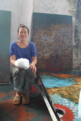 Phi Phi Oanh Nguyen, in her studio with her lacquer artwork, by Ravi Chandra