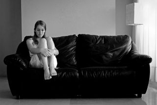 Sad woman sitting on when end of a couch with her knees folded up to her chest
