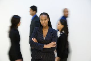businesswoman standing alone in front of people walking