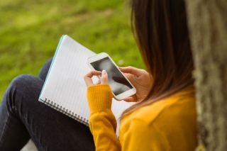 Female college student text messaging in the park