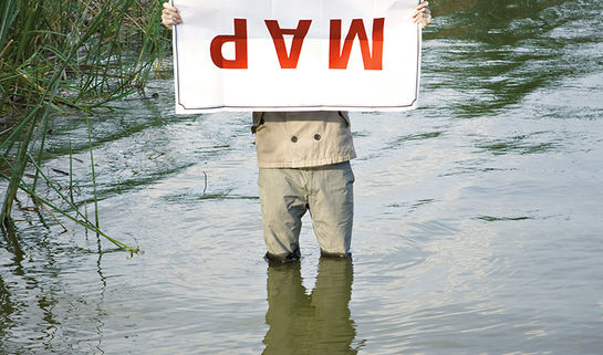 Image: Man holding a map upside down in the middle of a swamp