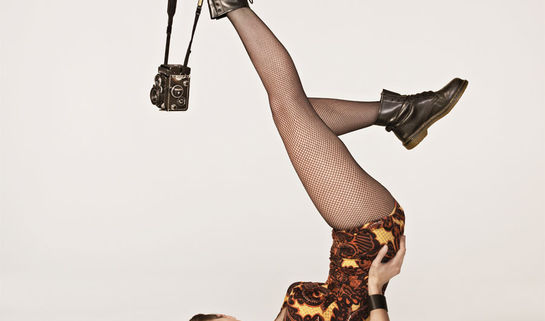 Image: young woman upside down in fishnets with a camera dangling off her foot