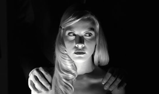 Image: Woman having her shoulders rubbed in the dark