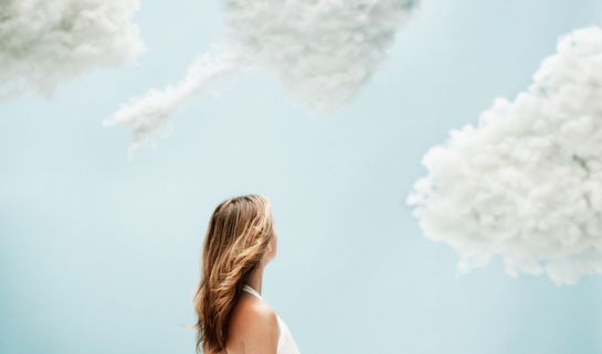 Image: Young woman observing heart shaped clouds in the sky