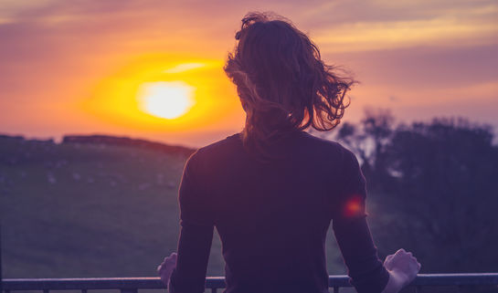Woman awed by sunset. Lolostock/Shutterstock
