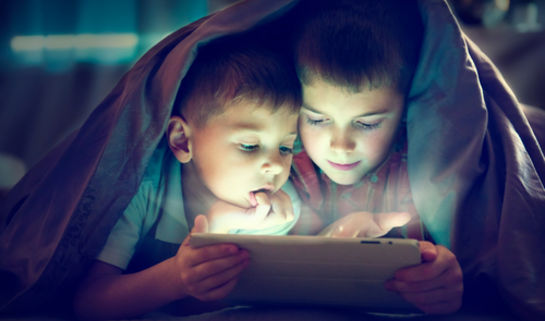 Two kids looking at a tablet under a blanket