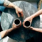 Man and woman holding cups on a table