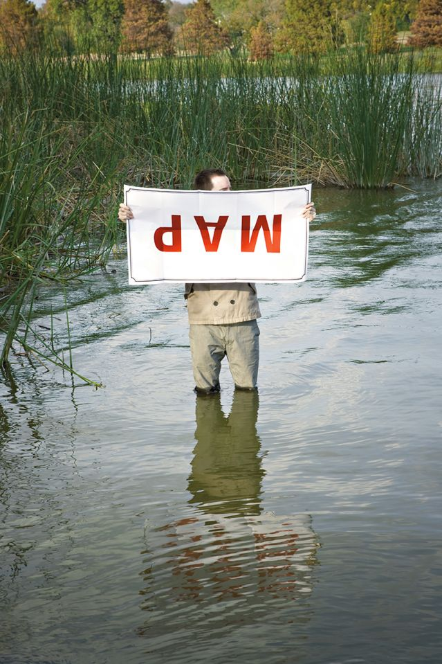 Man holding a map upside down in the middle of a swamp