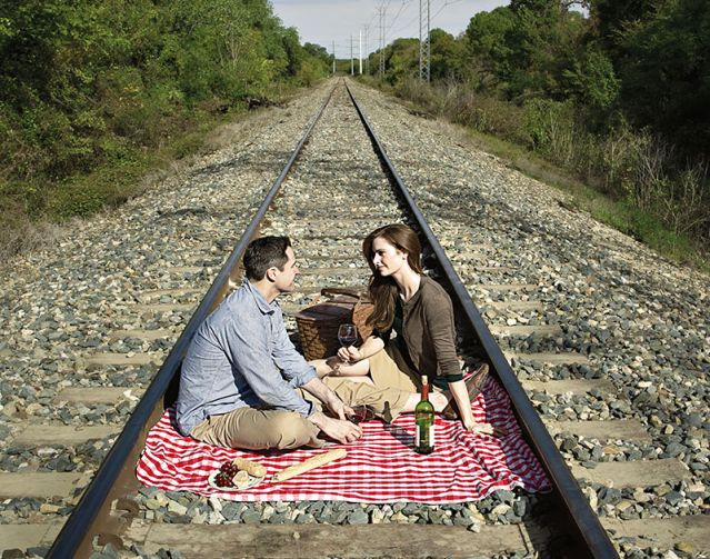 Couple picnicking on train tracks