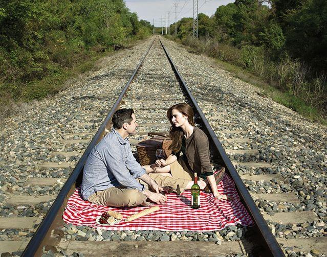 Couple picnicking on train tracks