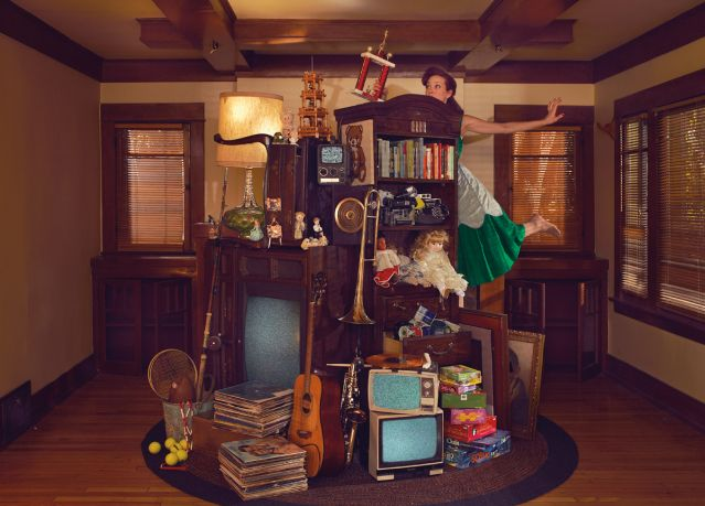 Woman balancing a pile of possessions in her living room