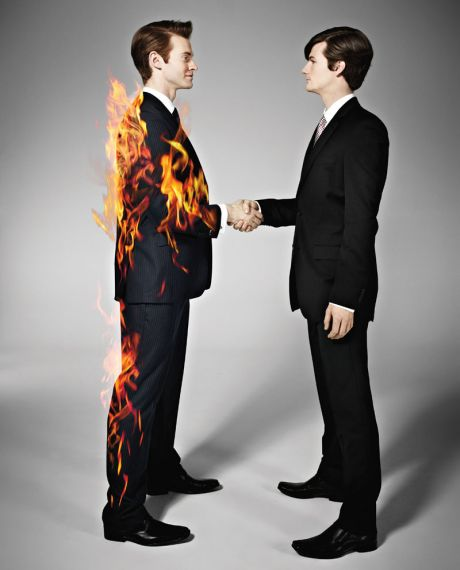 Man shaking the hand of another who is on fire