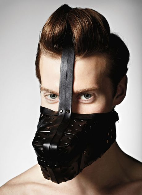 Man with a black leather muzzle on