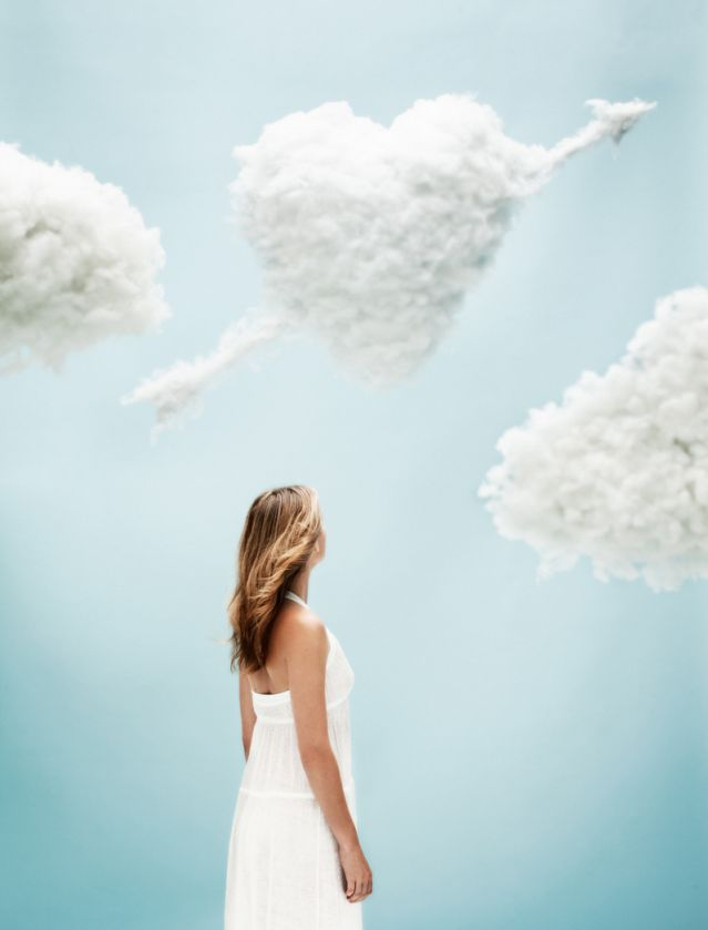 Young woman observing heart shaped clouds in the sky