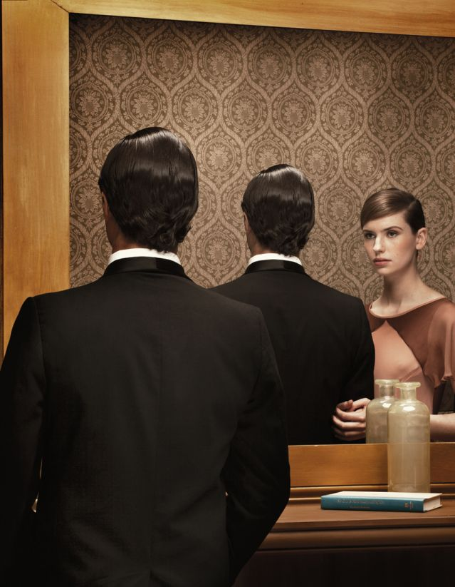 Man seeing a woman w/ him in his mirror reflection, when he's alone