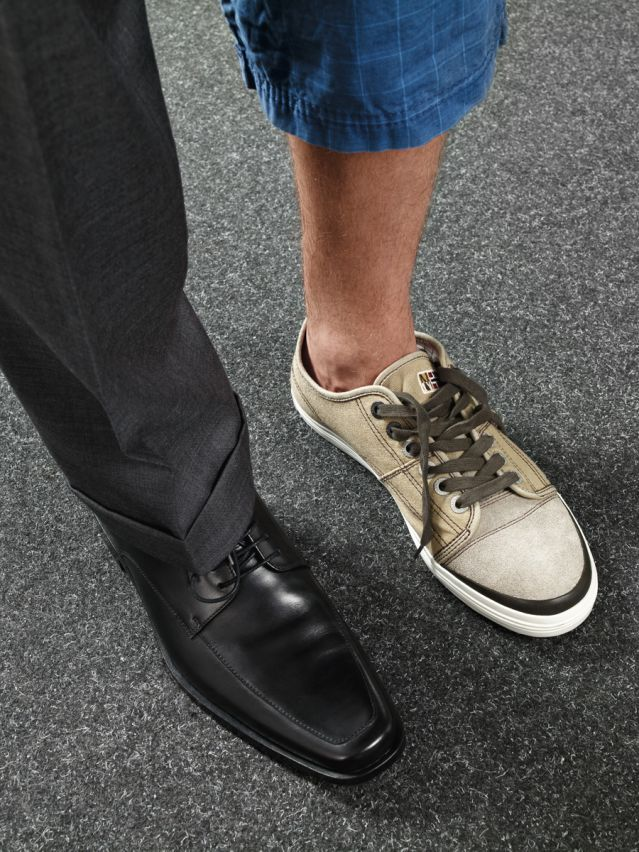 Man wearing dress shoe on one foot and sneaker on the other