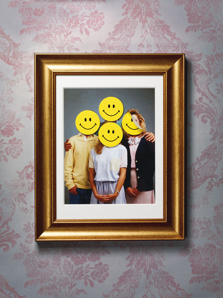 Family portrait with smiley faces stuck on the heads of family members