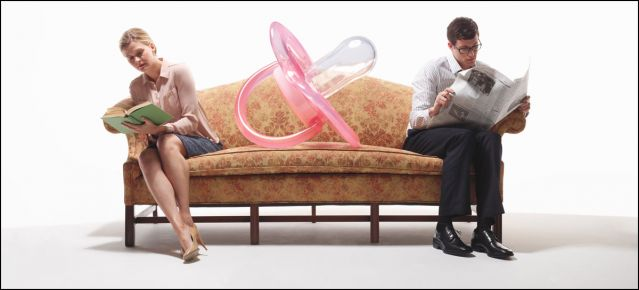 Mother and father at opposite ends of sofa with giant pacifier in middle