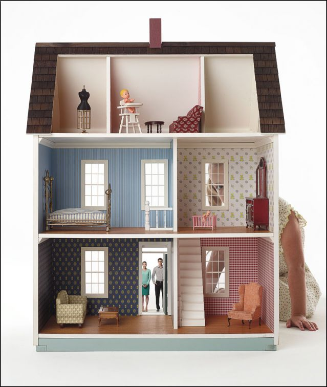Young girl hiding behind doll house