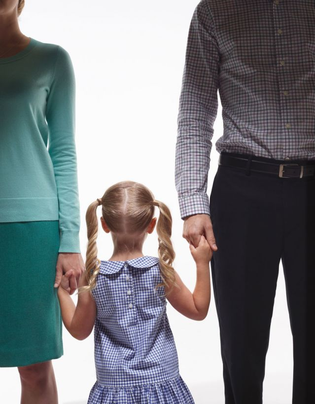 young girl holding both parents' hands