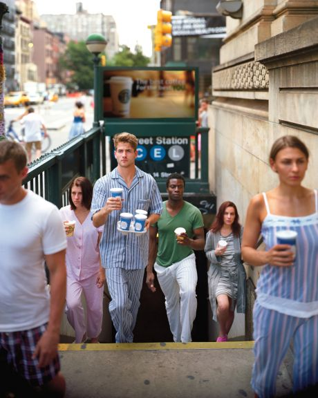 People emerging from subway in PJs w/ coffee