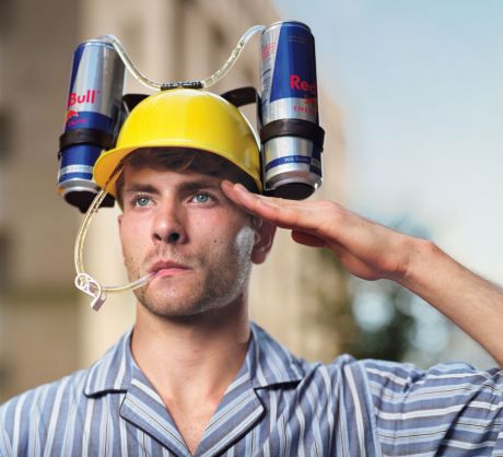 Man in hardhat holding 2 Red Bulls feeding into a straw