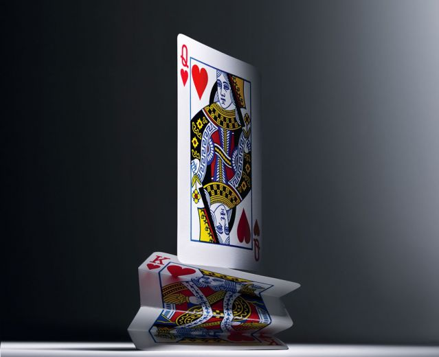 Queen of hearts card standing on top of smashed king of hearts card