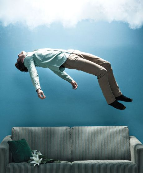 Man floating above a sofa into clouds
