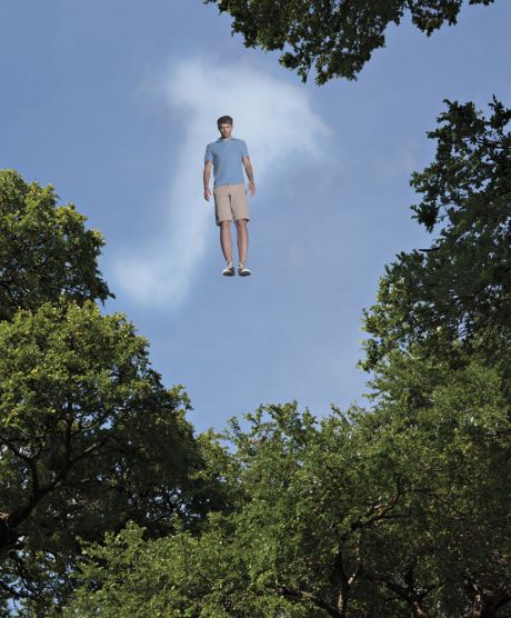 Man floating in sky above trees