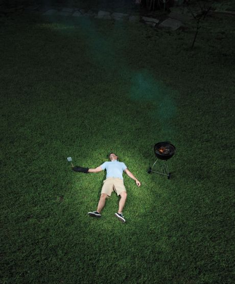 Man lying on ground with spatula next to grill
