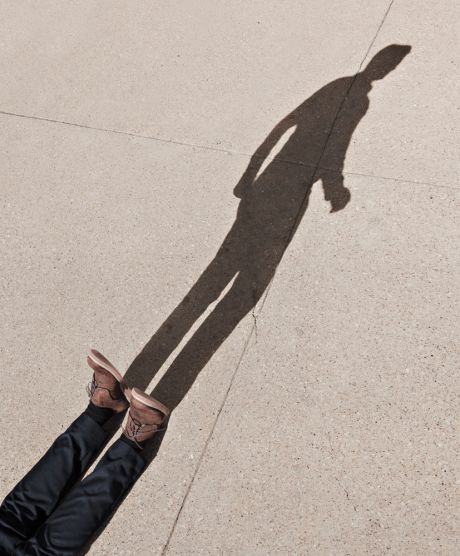 Man lying on ground but shadow is standing