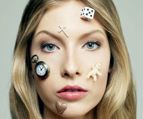 Young woman with icons of time, babies, gambling and love on her face