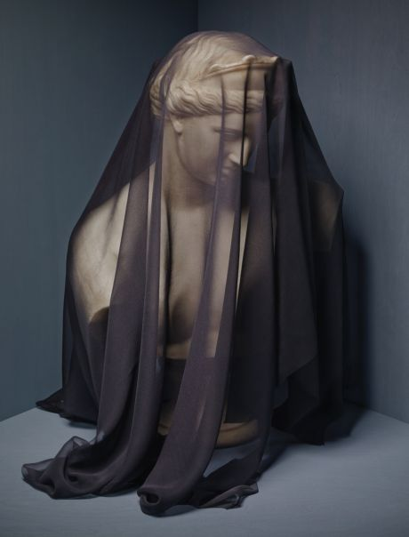 Statue of a woman's head draped with dark mourning fabric