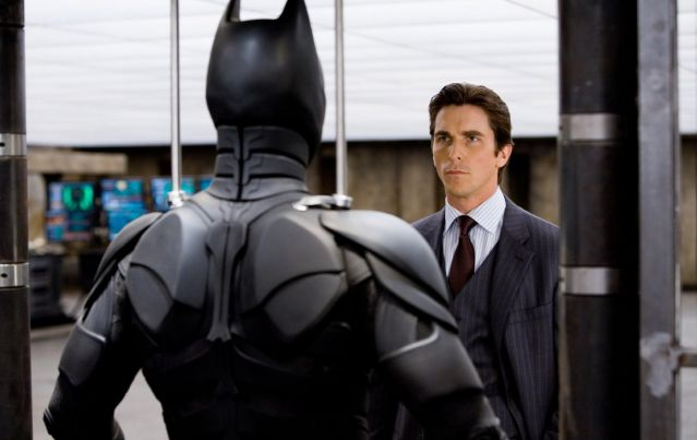 Christian Bale as Bruce Wayne faces his Batman suit.