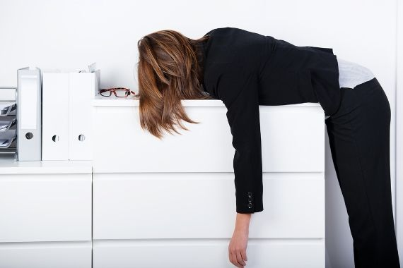 Woman slumped over photocopier sleeping
