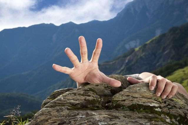 Hand reaching desperately over the top of a mountain