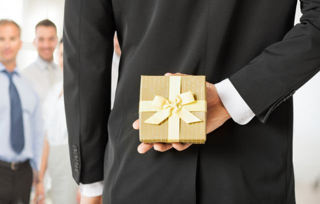 Business man facing team with gift behind his back