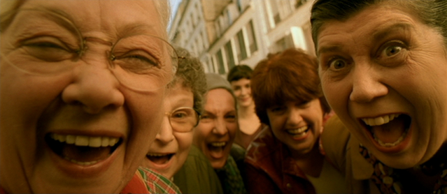 Crowd shot in Amélie, people laughing, social contagion