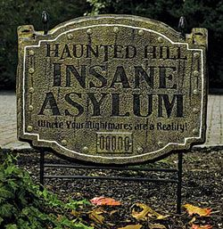 Yard sign that says Haunted Hill Insane Asylum