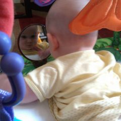 Image: Baby looking at her reflection in mirror