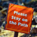 Sign reads please stay on the path