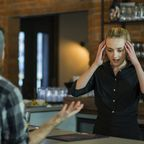 A server struggles to maintain her composure during a customer exchange.