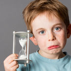 Purchased from Deposit Photos, Worried young child with pouting mouth holding an egg timer–© studiograndouest