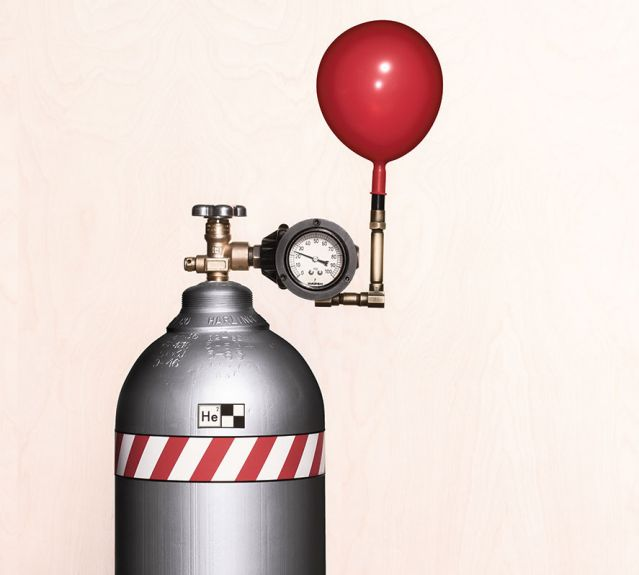 Red balloon beginning to inflate on helium tank