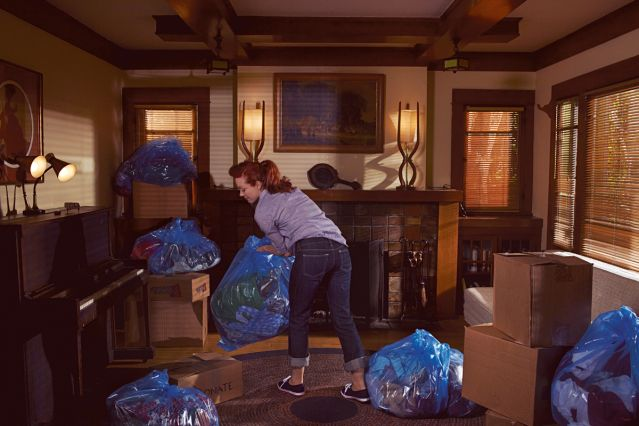 Woman cleaning house with garbage bags and donation boxes